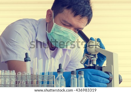 Chemist is analyzing sample in laboratory , using microscope. - stock photo