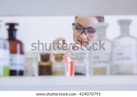 Chemist looking on test tube. Student in lab.