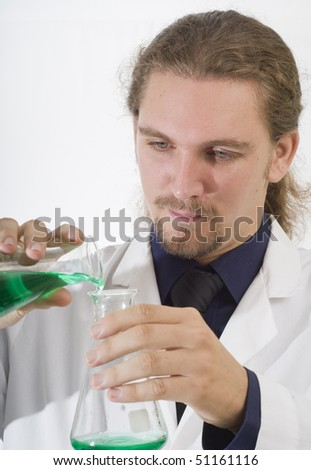 Chemist pouring chemicals in a laboratory - stock photo