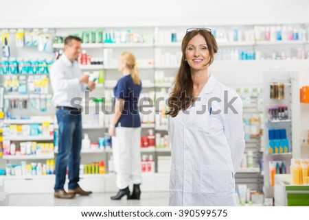 Chemist Smiling While Assistant And Customer Standing In Backgro - stock photo