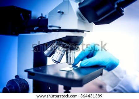 chemist testing samples with microscope and rubber gloves. Medical chemist in pharmaceutical field examining