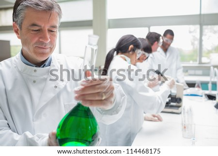 Chemist viewing liquid while other persons doing research in the laboratory - stock photo