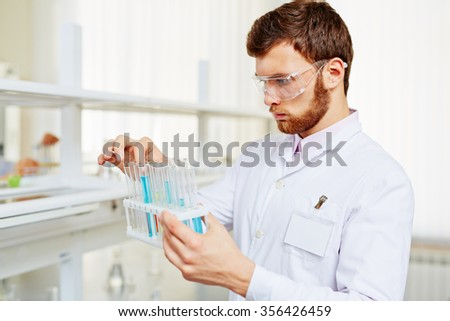 Chemist with flasks making experiment in scientific lab