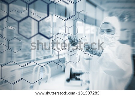 Chemist working cautiously with liquid helped by futuristic interface in soft focus effect - stock photo