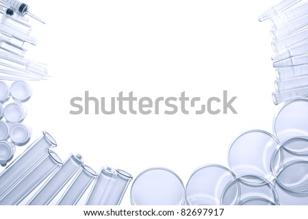 Chemistry laboratory equipment background of glass test tubes and Petri dishes with syringes and assorted experiment glassware in a science research lab with blank copy space in blue tone over white - stock photo