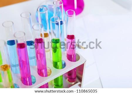Chemistry laboratory glassware with colour liquids in them - stock photo
