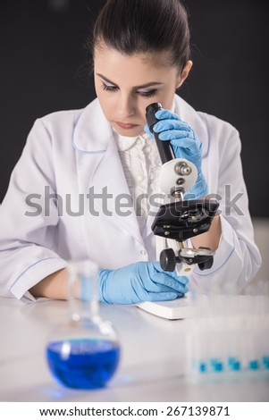 chemistry or science concept. Young beauty female doctor researcher using microscope. - stock photo