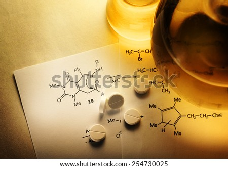 Chemistry reaction formula with white pills in closeup - stock photo