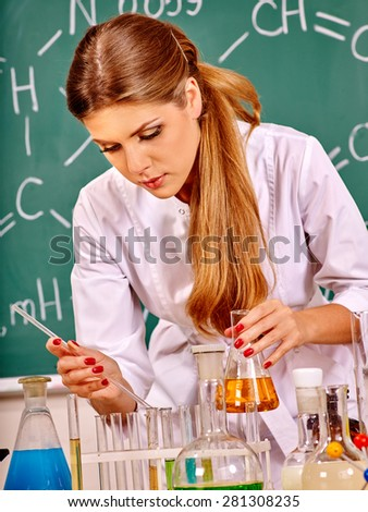 Chemistry teacher with test-tube working at chemistry classroom. - stock photo