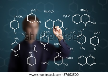 chemistry teacher writing scientific  formula of chemical on white board - stock photo
