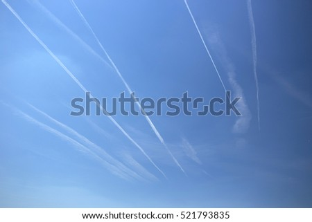 Chemtrails over the azure sky. Contrails over blue sky. Crisscrossing trails over sky. Jet trails, known as chemtrails or contrails over blue sky background