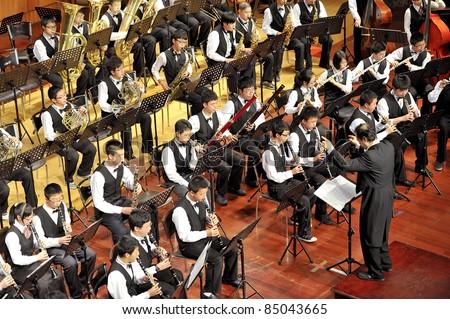 CHENGDU - APR 23: student symphonic band of High School No.7 Chengdu perform on concert on Apr 23,2011 in Chengdu,China. - stock photo