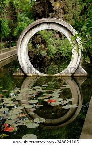 Chengdu, China - May 8, 2008:  A traditional Chinese moon gate reflected in a pond filled with water lilies at the Wenshu Temple gardens - stock photo