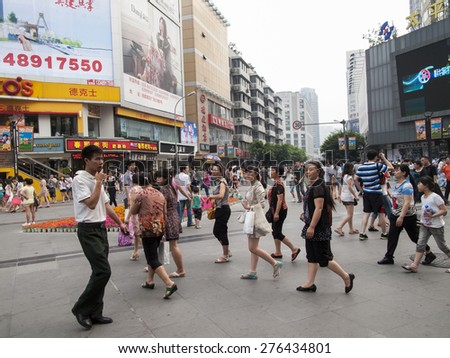 CHENGDU, CHINA - MAY 20, 2012: Unidentified people on the street of Chengdu, China. With more than 14 million people, Chengdu is the fourth most populous city in mainland China.