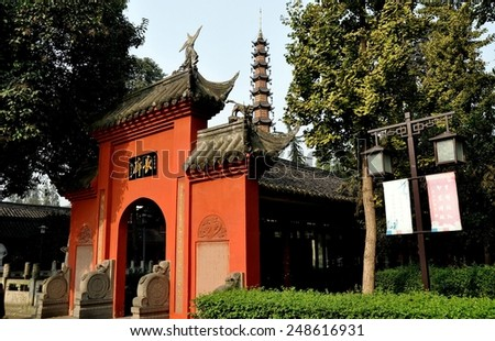 Chengdu, China - November 8, 2010:  Coral-colored entrance gate into the pagoda courtyard at the historic Wenshu Buddhist temple - stock photo
