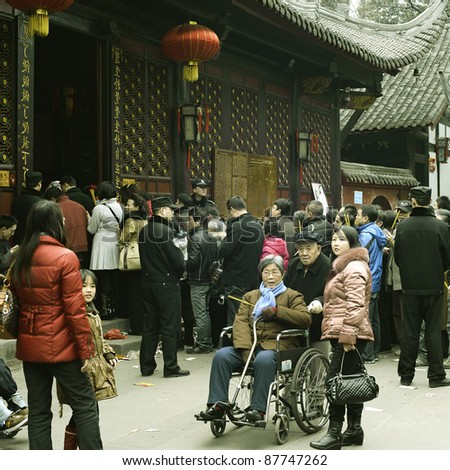CHENGDU - FEB 14: crowded People waiting in line to enter a temple to pray to Buddha during chinese new year on Feb 14, 2010 in Chengdu, China. It's part of the important traditional custom in China. - stock photo