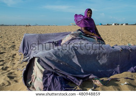 CHENNAI, INDIA - JULY 26, 2016: a girl sitting on the big pile of clothes at marina beach with her saree moving in motion blur on a windy day