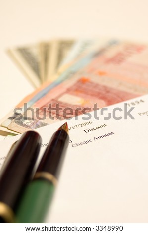 Cheque, money and pen, focus on first plane - stock photo