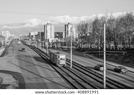 Cherepovets, Russia - April 11, 2016: Cars driving on the road, traffic in the spring morning. Black and white image - stock photo