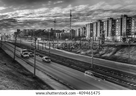 Cherepovets, Russia - April 11, 2016: Cars driving on the road, traffic in the spring morning. Typical cityscape with HDR technology. Black and white image - stock photo