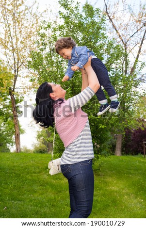 Cherful mom raising up his toddler son in park - stock photo
