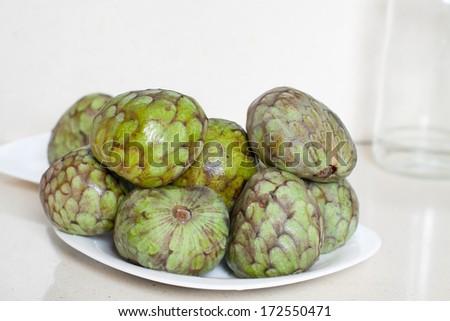 cherimoya on  saucer  on kitchen table - stock photo