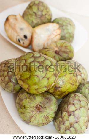 cherimoya on  saucers  on kitchen table - stock photo