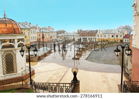 CHERNIVTSI, UKRAINE - APRIL 15, 2012: Tourists and locals like to spend their time next to the fountain on the Turkish Square in Chernivtsi, Ukraine