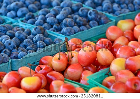 cherries and blueberries in aqua produce cartons - stock photo