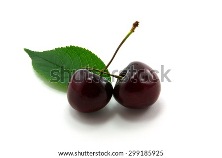 Cherries and green leaves isolated on white background