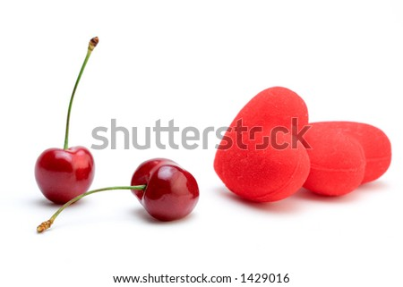 Cherries and hearts against white background - stock photo