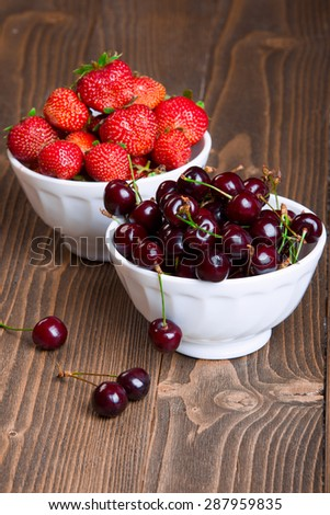 cherries and strawberries in white bowls on a wooden background