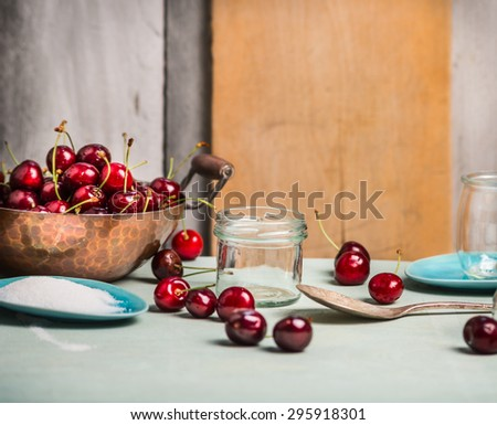 Cherries berries preserving with glass jar on rustic kitchen table, over wooden background - stock photo