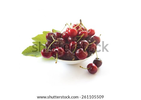 Cherries in a white bowl on white background - stock photo