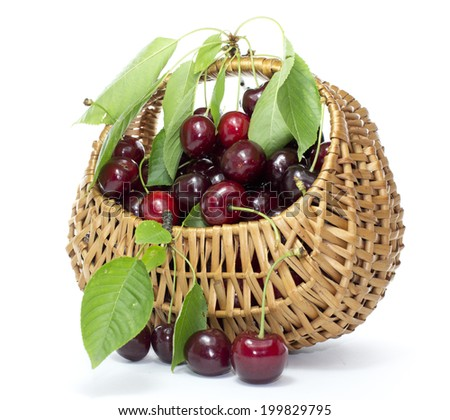 Cherries in a wicker basket with a leaf on a white background - stock photo