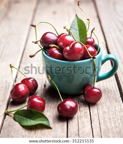 Cherries in the beautiful turquoise cup on wooden table, macro background, fruits, berries - stock photo
