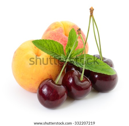 Cherries, leaves and peaches on a white background. - stock photo