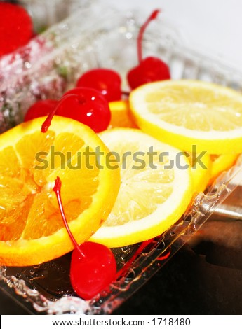 Cherries, lemons, oranges, and strawberries in a plastic container