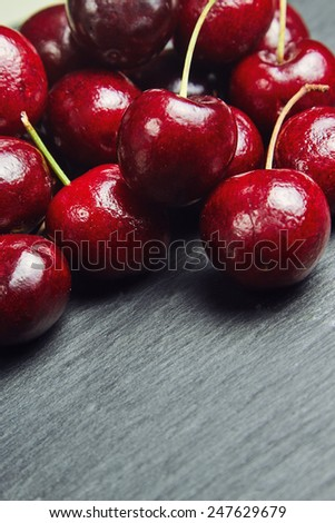 Cherries on a black slate with space for text - stock photo
