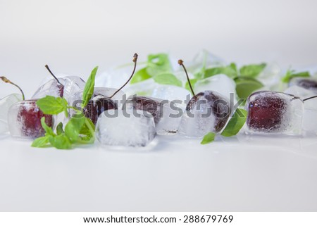 cherry and ice cubes with mint leaves - stock photo
