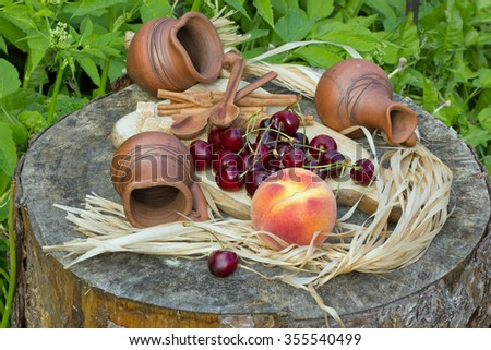 cherry and peach on a wooden stump and three ceramic pitcher