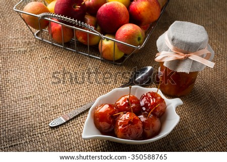 Cherry apples covered in syrup on white saucer, spoon, jar of homemade marmalade and apples in metal wire basket on a burlap. Apple fruit confiture jam marmalade.  - stock photo