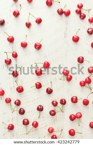Cherry background. Red cherries scattered on rustic table. Overhead view, blank space  - stock photo