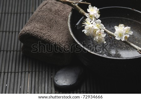 cherry blossom flowers in bowl with black stone with towel on mat - stock photo