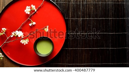 Cherry blossoms and green tea on the Japanese red tray - stock photo