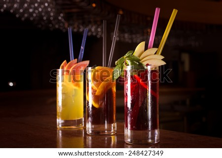 Cherry bomb, screwdriver and cuba libre cocktails in a tall glasses on the dark background. Shallow DOF and dark red tone - stock photo