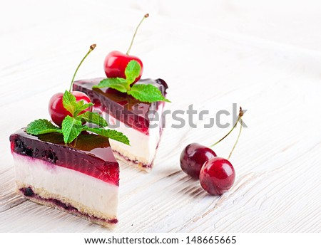 Cherry cheesecake with tea on a wooden table - stock photo