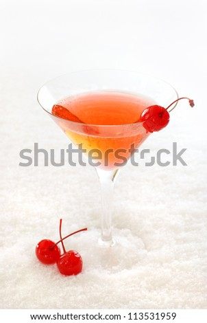 Cherry cocktail in a martini glass decorated with maraschino cherries, on snow. - stock photo