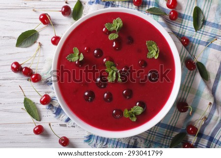 cherry cream soup with mint in a bowl on a table close-up. Horizontal top view  - stock photo