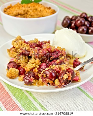 Cherry crumble in a white bowl and a plate with a spoon, cherries on a background of striped linen tablecloth - stock photo